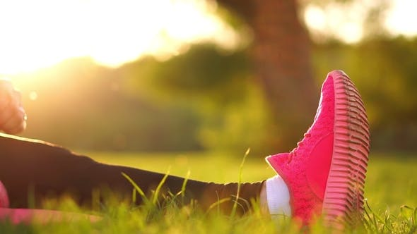 Thumbnail for Hands Take over the Sole of the Sneakers on the Grass in Sunlight
