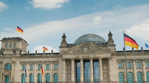 The Building of the Bundestag in Berlin. Flags Develop in the Wind