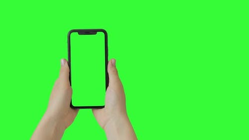 Girl hands holding the smartphone on green screen chroma key background. Vertical orientation.