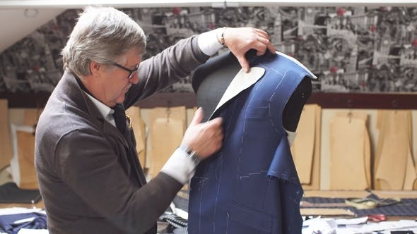 Thumbnail for Professional Mature Tailor Working on His New Classical Suit Using Tailor's Dummy at His Workshop.