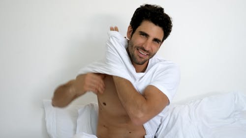 Man Undressing in Bed