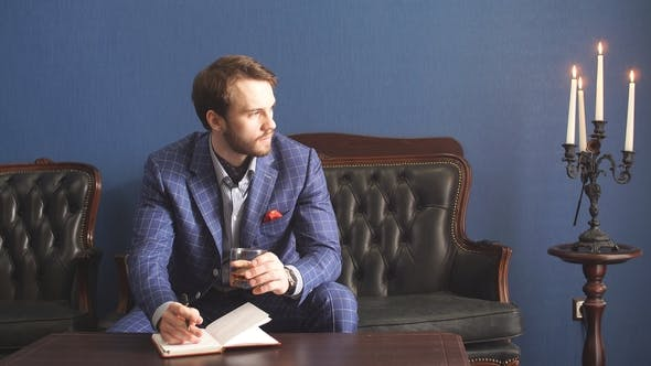 Thumbnail for Handsome Young Man in a Classic Suit Drinking Whiskey in Restaurant and Makes Notes in a Notebook.