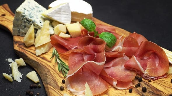 Cover Image for Sliced Prosciutto and Cheese on a Wooden Board