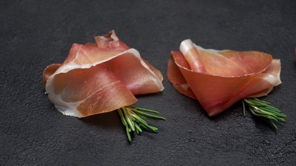 Thumbnail for Sliced Prosciutto or Jamon Meat on Dark Concrete Background