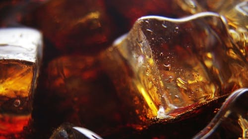 Ice Cubes in a Glass of Coke and Bubbles Rising