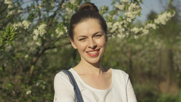 Thumbnail for Smiling Beautiful Woman Near Blossoming Tree