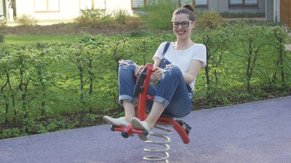 Cover Image for Attractive Woman Riding Spring Toy on Playground