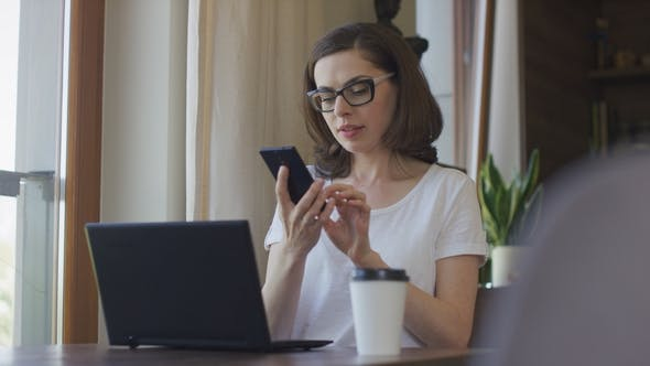 Thumbnail for Attractive Woman Using Smartphone and Laptop at Home