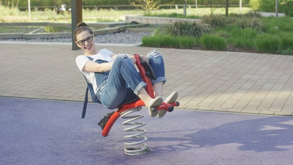 Thumbnail for Smiling Woman Riding Spring Toy on Playground