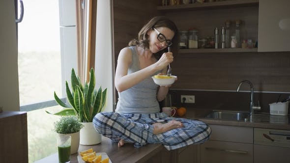 Thumbnail for Attractive Woman Sitting on Table and Eating Breakfast