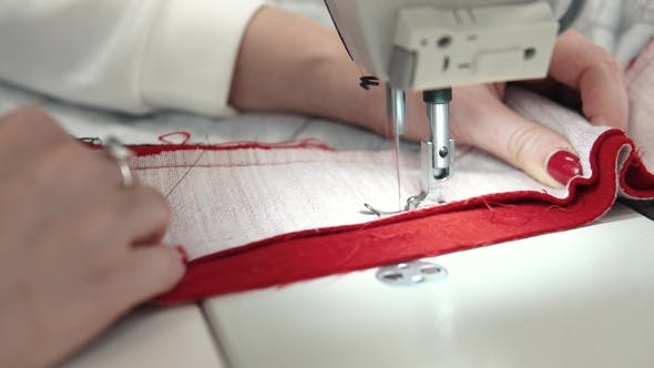 Thumbnail for Woman Sews on a Sewing Machine