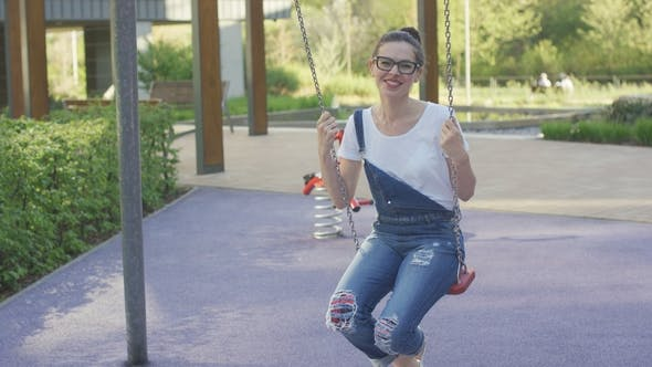 Thumbnail for Attractive Smiling Woman Swinging on Playground