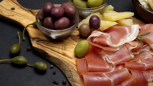 Cover Image for Sliced Prosciutto on a Wooden Board and Bread