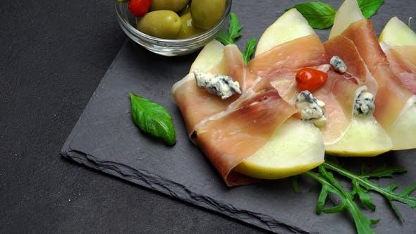Cover Image for Sliced Prosciutto and Melon on a Stone Board