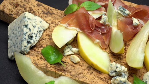 Cover Image for Sliced Prosciutto and Melon on a Cork Wooden Board