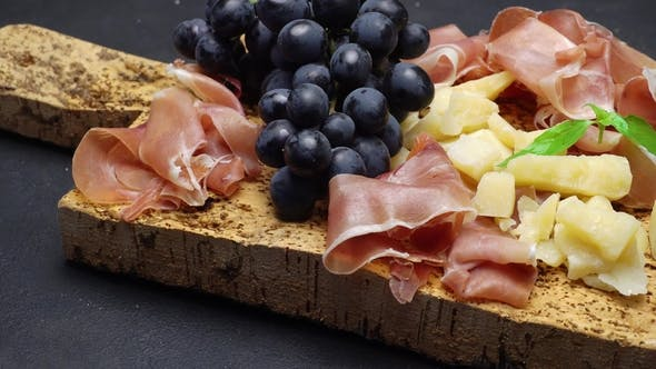 Cover Image for Sliced Prosciutto or Jamon Meat and Cheese on Cork Wooden Board