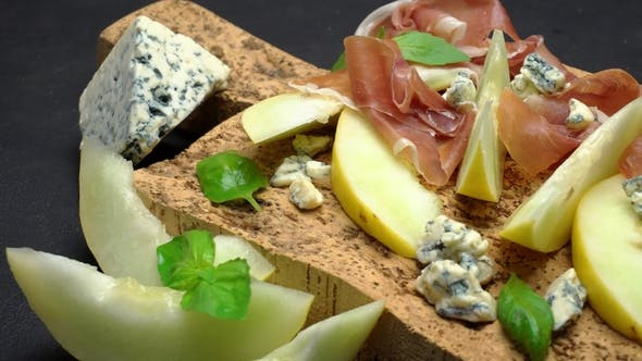 Thumbnail for Sliced Prosciutto and Melon on a Cork Wooden Board