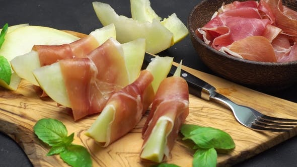 Thumbnail for Sliced Prosciutto and Melon on a Wooden Board