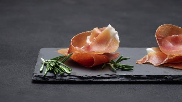 Cover Image for Sliced Prosciutto or Jamon Meat on Dark Concrete Background
