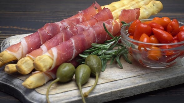 Cover Image for Italian Grissini with Prosciutto, Capers and Pepper on Wooden Cutting Board