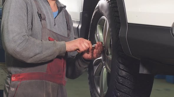 Thumbnail for Auto Mechanic Is Twisting Manually Bolts of a Wheels on an Automobile, Raised By Lifting Equipment.