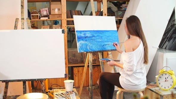 Thumbnail for A Young Female Artist Painting Picture on Canvas with Blue Oil Paints in Her Workshop.