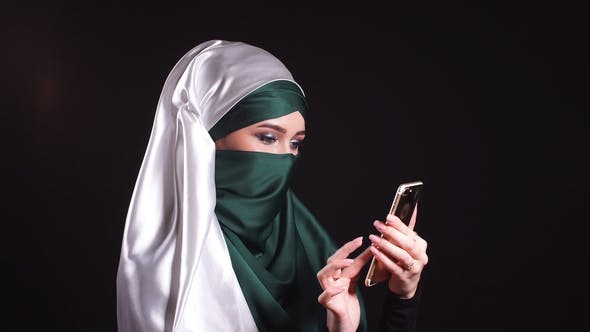 Thumbnail for Portrait of Happy Muslim Woman Using Mobile Phone.