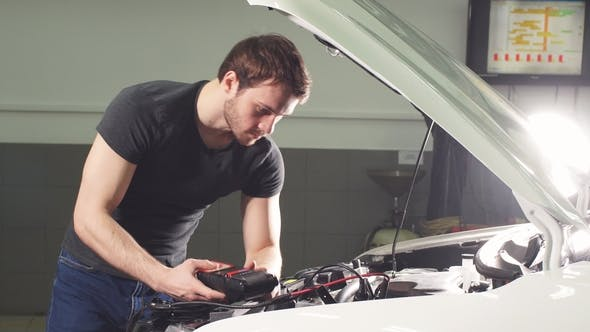 Cover Image for Car Mechanic Is Standing in an Auto Repair Shop Near Automobile with Open Hood and Making Notes.