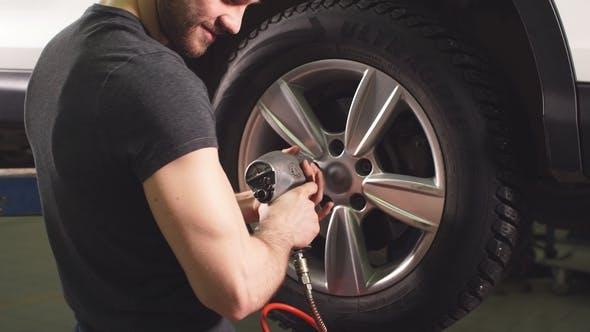 Thumbnail for Car Mechanic Changing Car Wheel in Auto Repair Garage.