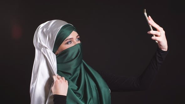 Thumbnail for Young Muslim Girl in Hijab Doing Selfie on Mobile Phone Camera.