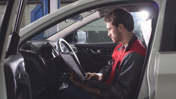 Thumbnail for The Repairman, Who Is Dressed in a Working Uniform, Is in the Vehicle and Checks the Gearbox.