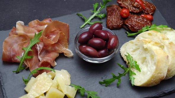 Cover Image for Sliced Prosciutto or Jamon Meat and Cheese on Concrete Background
