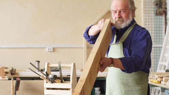 Thumbnail for Old Male in Special Clothes Using Planks in Building in the Workshop.