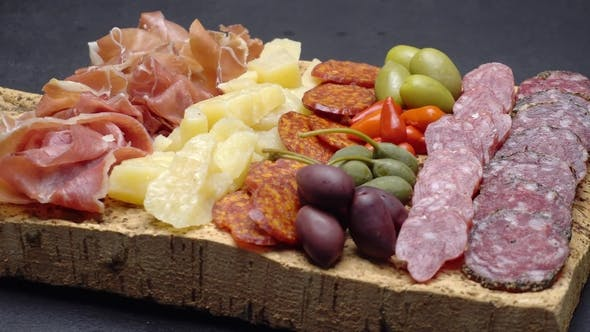 Thumbnail for Sliced Prosciutto, Cheese and Salami Sausage on Cork Wooden Cutting Board