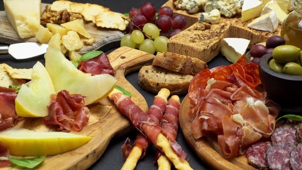 Cover Image for Meat and Cheese Plate Antipasti Snack with Prosciutto, Melon, Grapes and Cheese