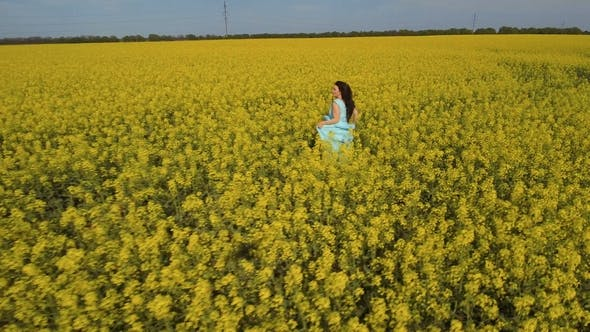 Thumbnail for Beautiful Woman in Blue Dress Runs through a Yellow Field with Canola Flowers