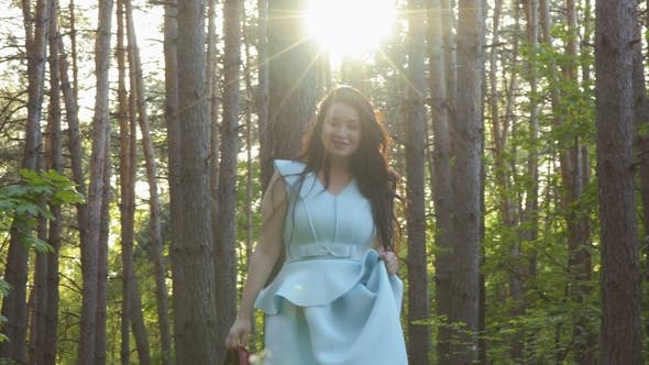 Thumbnail for Charming Brunette in Blue Dress Walks in Forest Holding Her Red Shoes in Hand