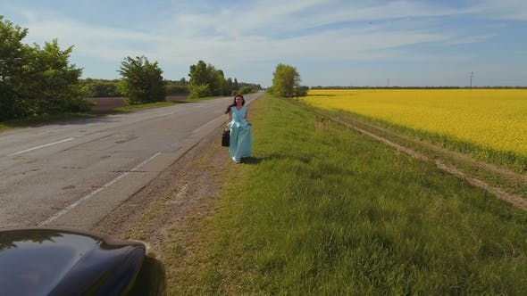 Thumbnail for Beautiful Brunette in Long Blue Dress Hold Suitcase in Hand and Goes To Her Car