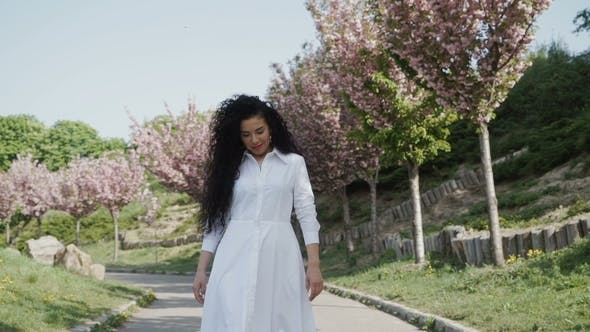Thumbnail for Beautiful Curly Brunette in White Dress Walking in Blooming Park