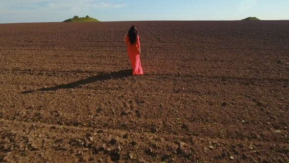 Thumbnail for Girl in Long Red Dress Walk Through Plowed Field