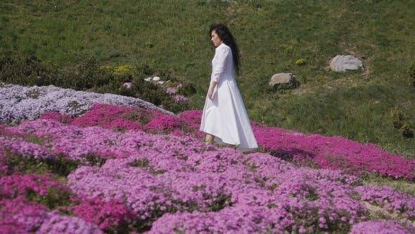 Thumbnail for Charmante Brünette Spaziergänge unter rosa Blumenbeeten im Botanischen Garten