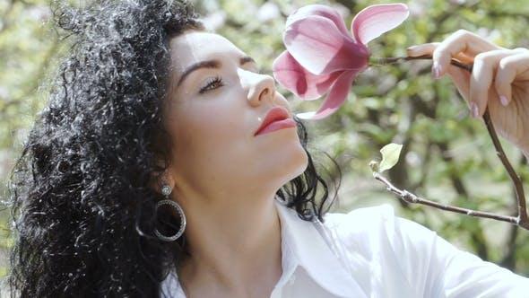 Thumbnail for Charming Curly Brunette Enjoy Smell of Magnolia Flower