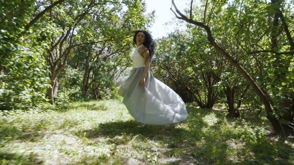 Thumbnail for Beautiful Brunette in Blue Dress Run Through a Garden,