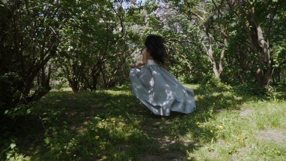 Thumbnail for Beautiful Brunette in Long Blue Dress Run Through a Garden