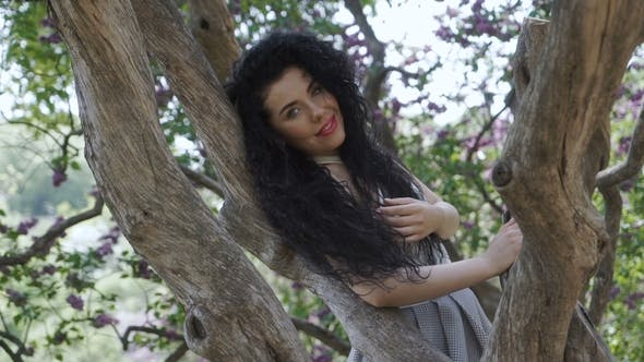 Thumbnail for Gorgeous Model Posing for Camera Leaning on Dried Tree Trunk