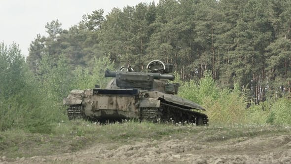 Military Tank in Movement on a Dirt Ground Terrain