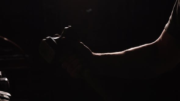 Cover Image for Man's Hand Throws a Hammer and Rotates It on a Dark Background in the Contour Light