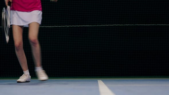Cover Image for Woman in a Pink T-shirt and a White Skirt Plays Off the Balls during a Tennis Match