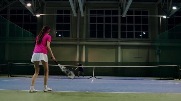 Thumbnail for Frau in einem rosa T-shirt und einem weißen Rock spielt aus den Bällen während eines Tennisspiels