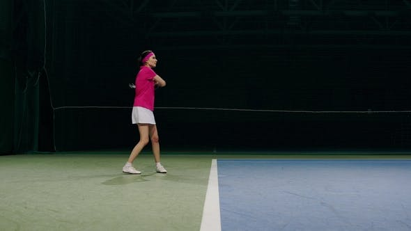 Thumbnail for Woman in a Pink T-shirt and a White Skirt Plays Off the Balls during a Tennis Match